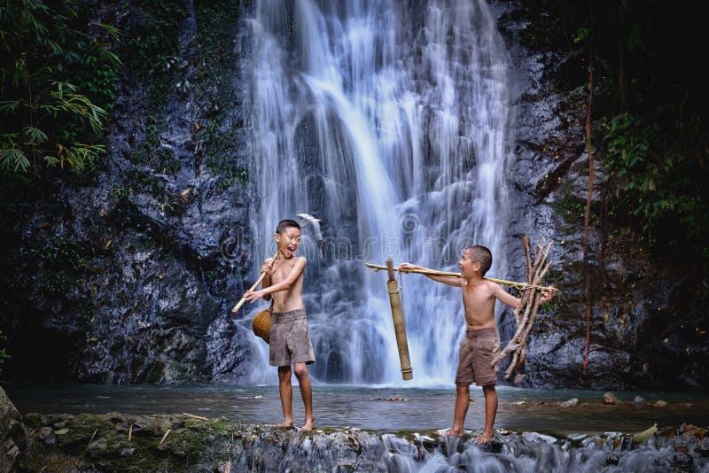 两个男孩在瀑布乡下泰国的笑渔 Fishin 免版税库存照片