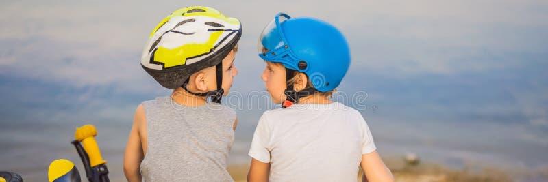 两个男孩坐湖的岸在乘坐自行车和滑行车横幅以后,长的格式 库存图片