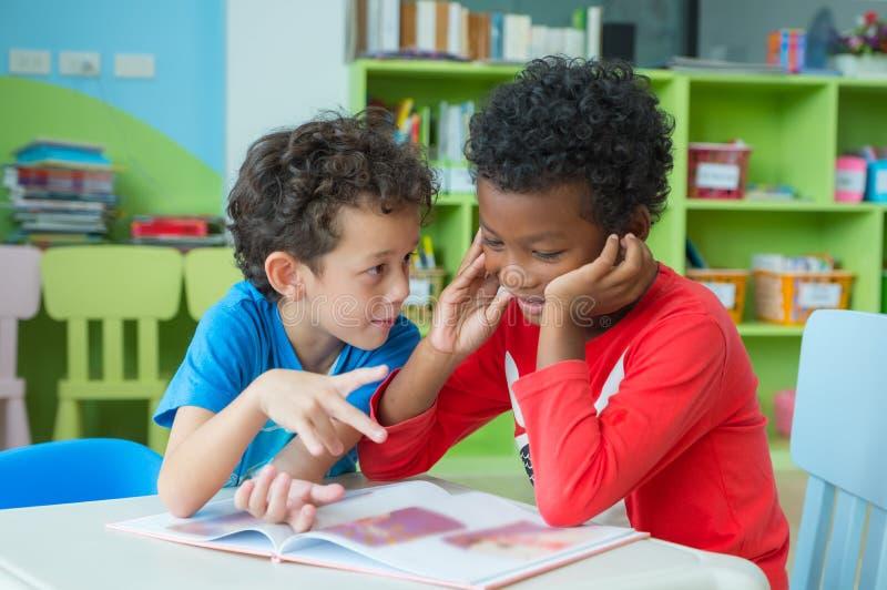 两个男孩孩子坐桌和着色在书在学龄前图书馆里,幼儿园学校教育概念 免版税图库摄影