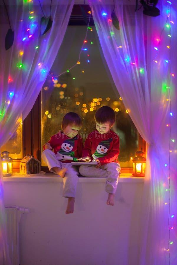 两个男孩,使用在窗口的片剂 库存照片