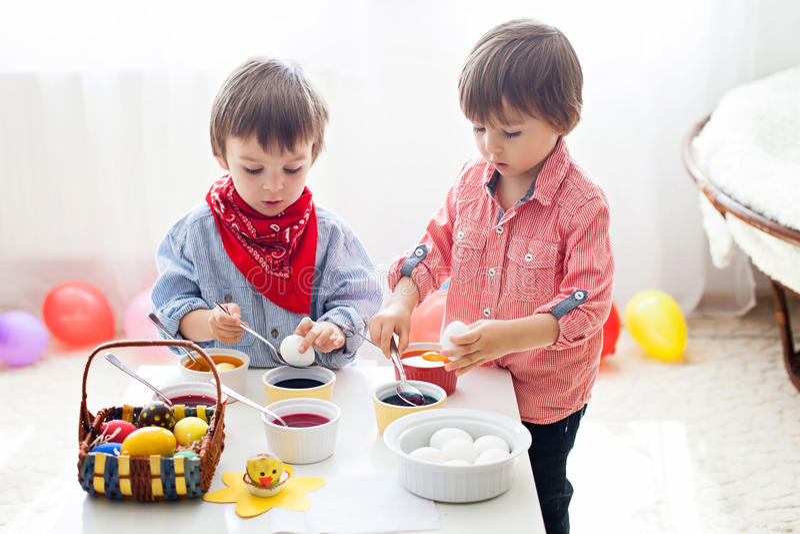 两个男孩,复活节的上色鸡蛋在家 免版税图库摄影
