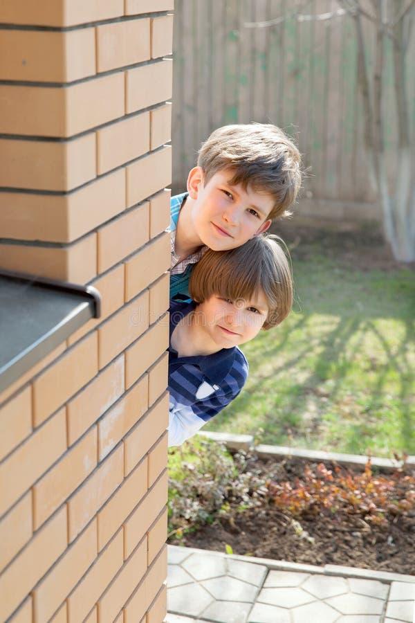 两个男孩从砖墙看  免版税库存照片