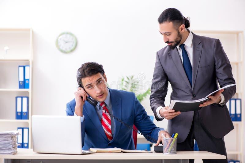 两个男性同事在办公室 免版税库存照片