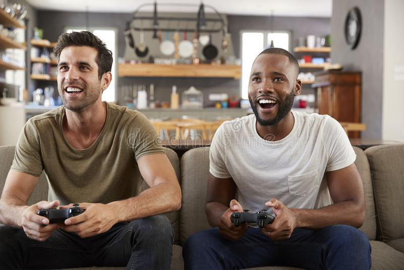 两个男性朋友坐沙发在打电子游戏的休息室 免版税库存图片
