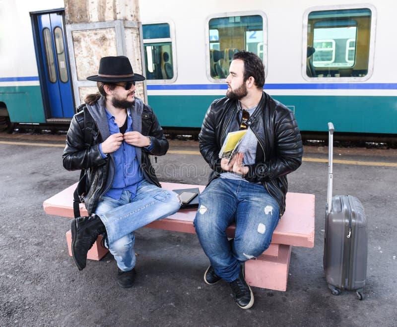两个男性朋友游人坐并且争论 库存图片