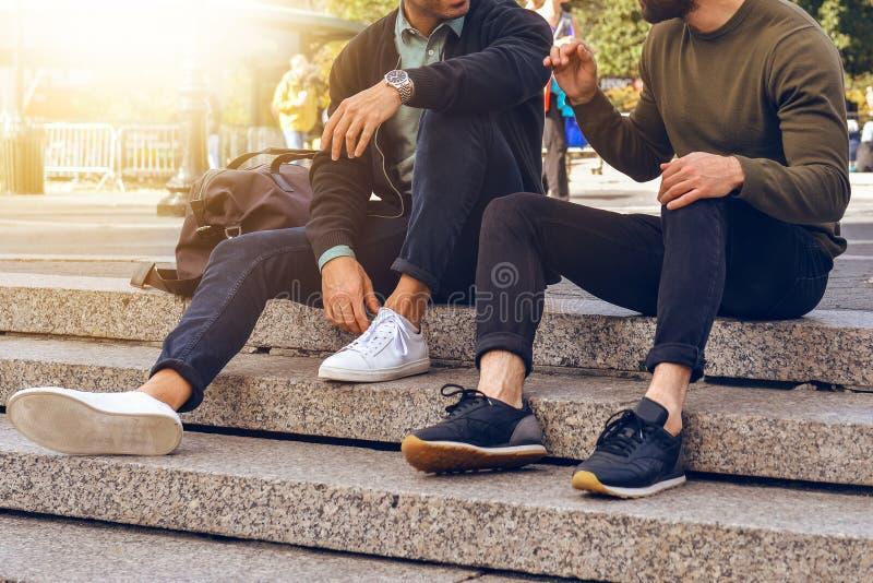 两个男性朋友生活方式照片坐在城市街道的步和谈的佩带的偶然街道样式衣裳和sneake 免版税图库摄影