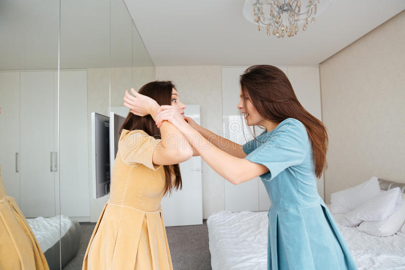 两个疯狂的被激怒的年轻姐妹在卧室孪生争论 库存图片