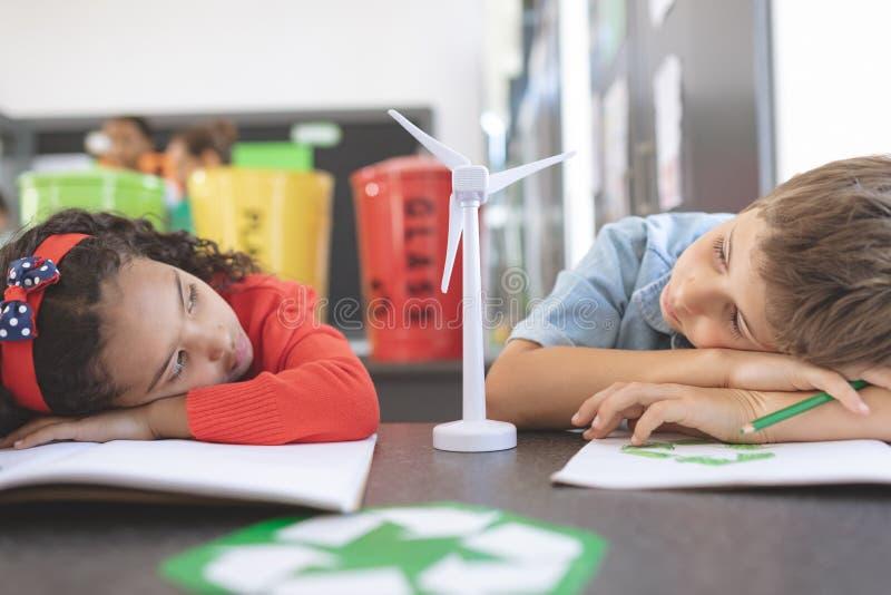 两个疲乏的学校孩子观察在他们之间的一个风车大模型 免版税库存图片