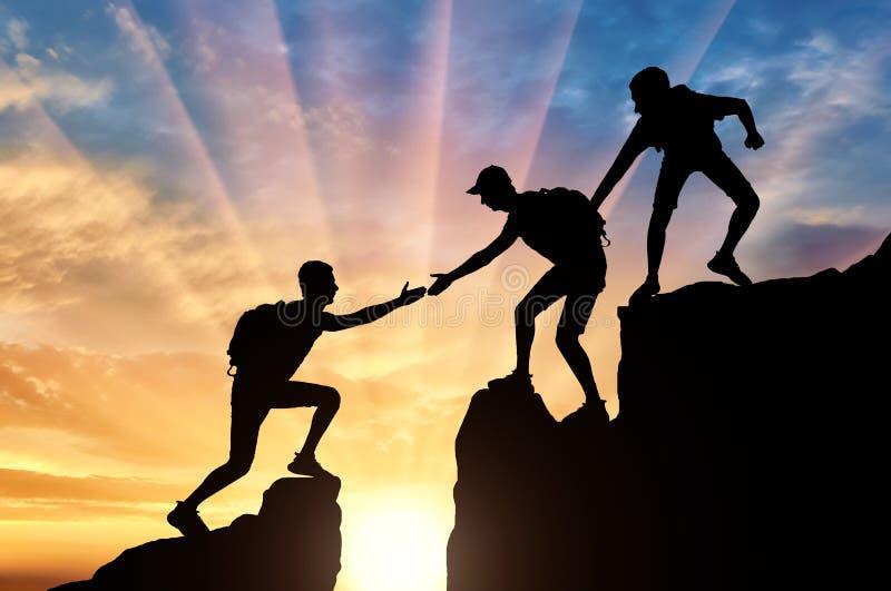 两个登山人剪影山的帮助另一个登山人克服障碍 皇族释放例证