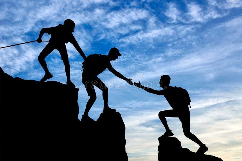 两个登山人剪影山的帮助另一个登山人 向量例证