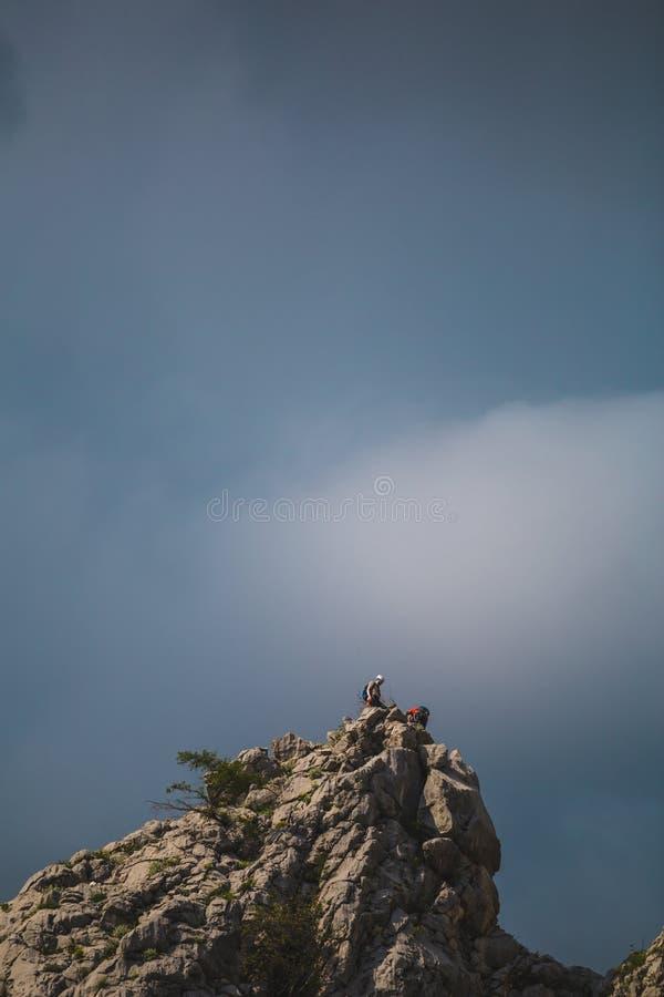 两个登山人在山的上面上升 免版税库存照片