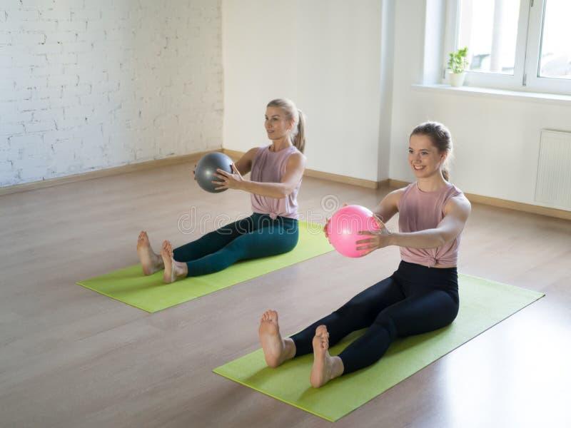 两个白种人女孩在健身演播室实践与小适合的球的pilates,顶楼样式,选择聚焦 免版税库存图片