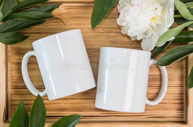两个白色杯子,婚姻大模型的杯子 免版税库存图片