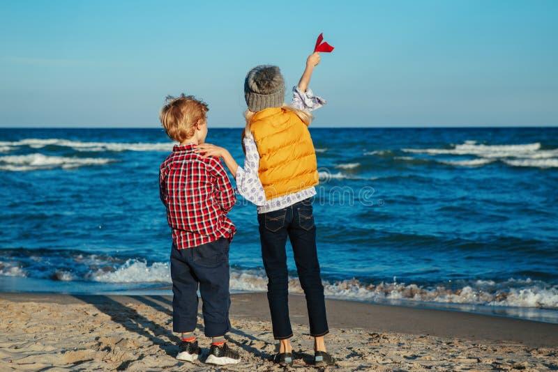两个白色白种人儿童孩子、更老的演奏在海洋海海滩的姐妹和弟弟纸飞机在日落 免版税库存照片