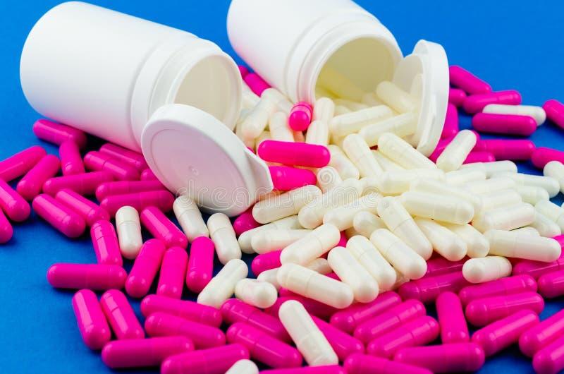 两个白色药片瓶子和疏散桃红色和白色胶囊在蓝色背景 免版税库存图片