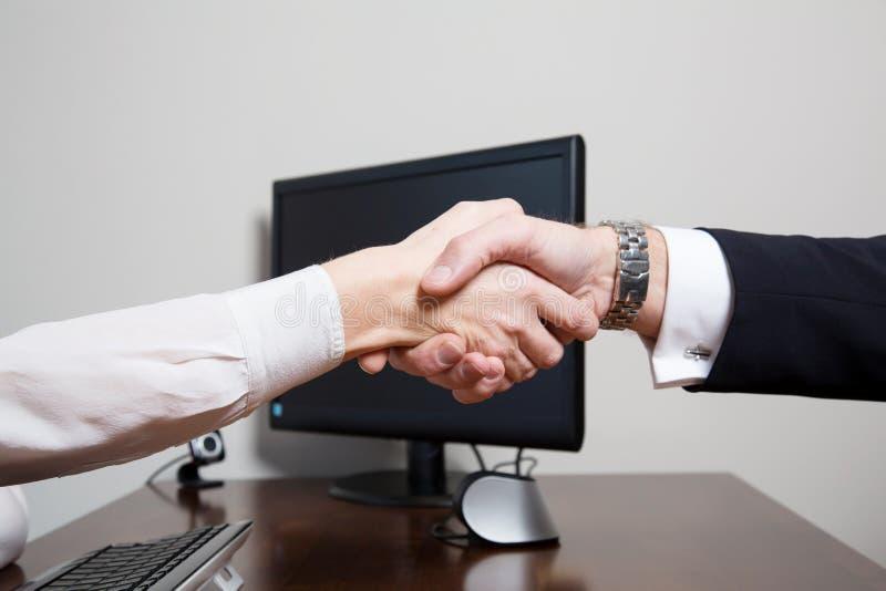 两个相等的同事握手在书桌的 免版税库存图片