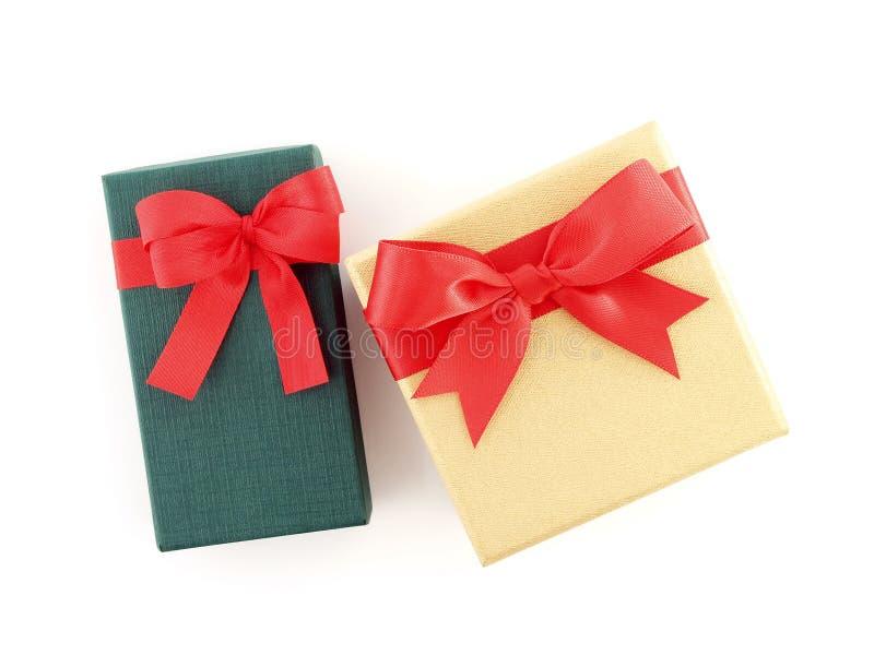 两个礼物盒绿色和金黄与在白色背景隔绝的红色丝带弓 图库摄影