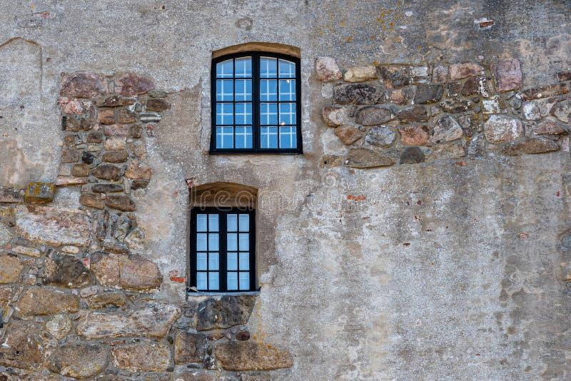 两个窗口水平的框架在一个老粗砺的古老中世纪石墙上的在瓦尔贝里堡垒在瑞典 免版税图库摄影