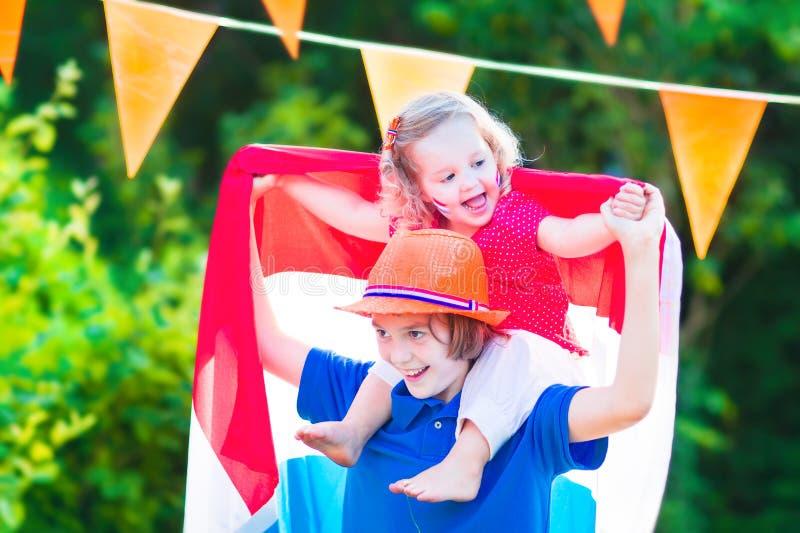 两个笑的滑稽的孩子荷兰橄榄球支持者 免版税库存图片
