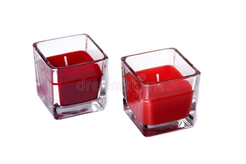 两个红色玻璃蜡烛,在白色隔绝的一个对五颜六色的茶光 免版税库存照片