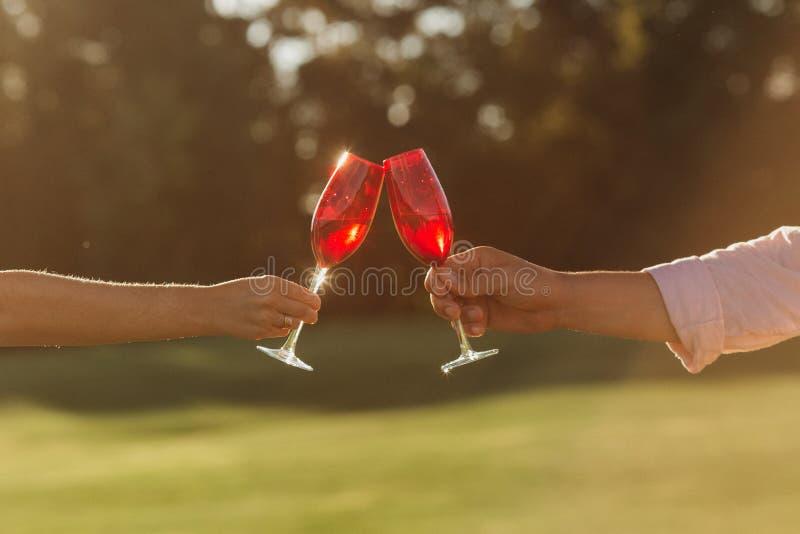 两个红酒酒杯在妇女手和人手上在自然背景 免版税库存图片