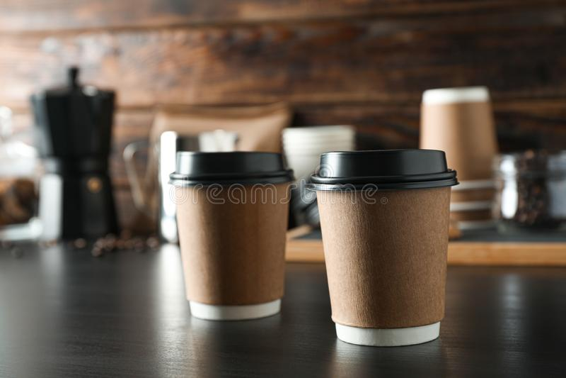 两个纸玻璃和咖啡时间辅助部件在黑桌上反对木背景,空间文本的 免版税图库摄影
