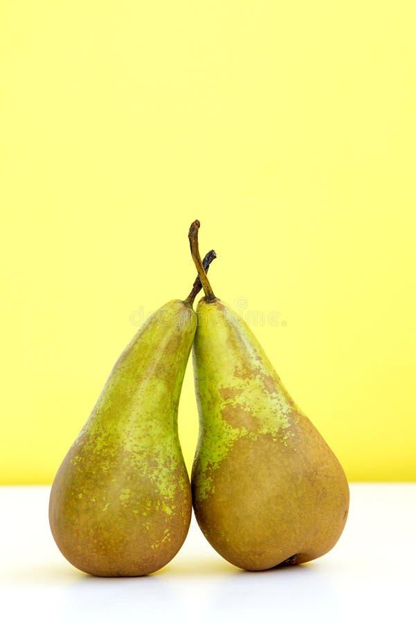 两个绿色成熟梨紧挨着在黄色时兴的背景 库存图片