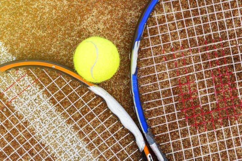 两个网球拍顶面顶上的看法有球的以户外法院概念为基础 免版税库存照片