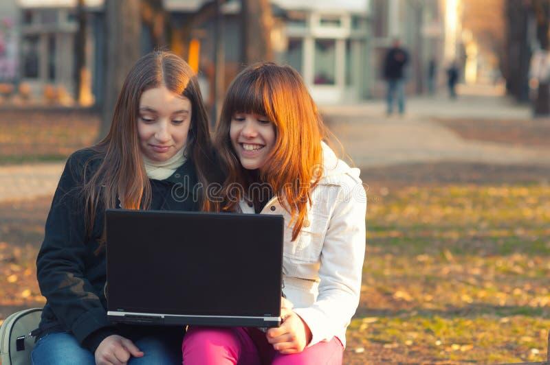 两个美丽的十几岁的女孩获得与笔记本的乐趣在公园 免版税库存照片