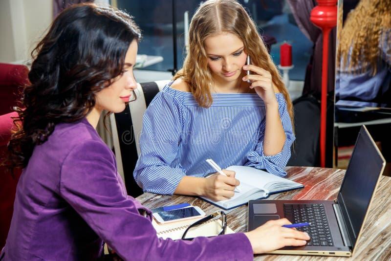 两个美丽的女学生为在咖啡馆的研讨会准备着 免版税图库摄影