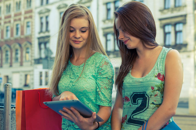 两个美丽的女孩坐与片剂个人计算机的一条长凳 库存照片