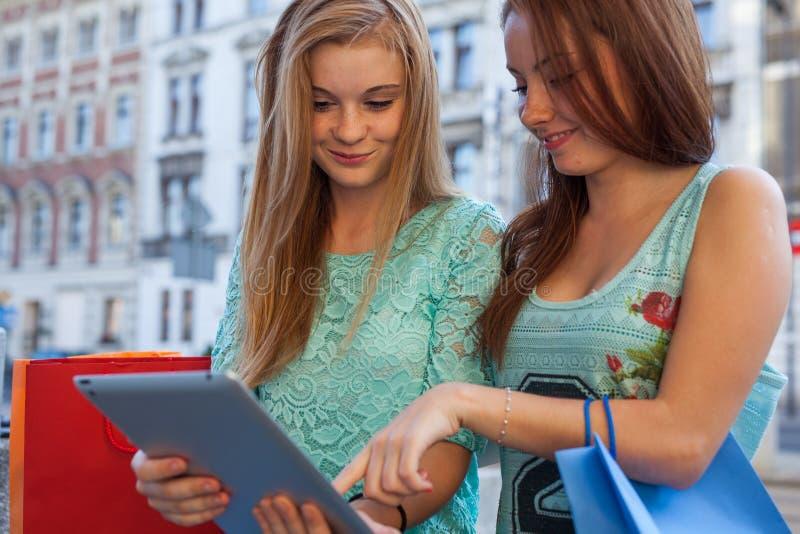 两个美丽的女孩坐与片剂个人计算机的一条长凳 免版税图库摄影