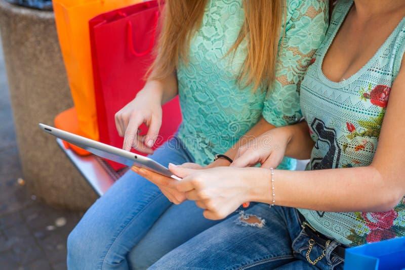 两个美丽的女孩坐与片剂个人计算机的一条长凳 免版税库存图片