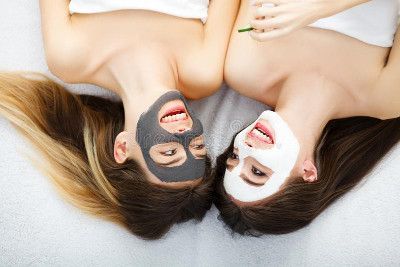 两个美丽的女孩画象有面部奶油的在他们的面孔 库存图片