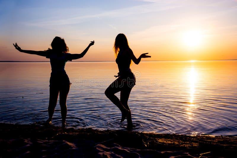两个美丽的女孩,学生在海滩跳舞在日落 库存图片