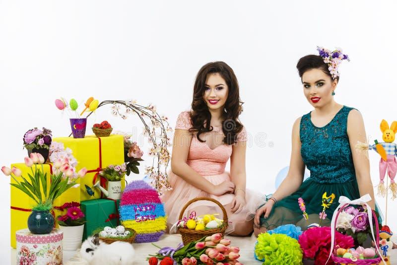 两个美丽的女朋友女孩、篮子用鸡蛋和花deco 库存图片