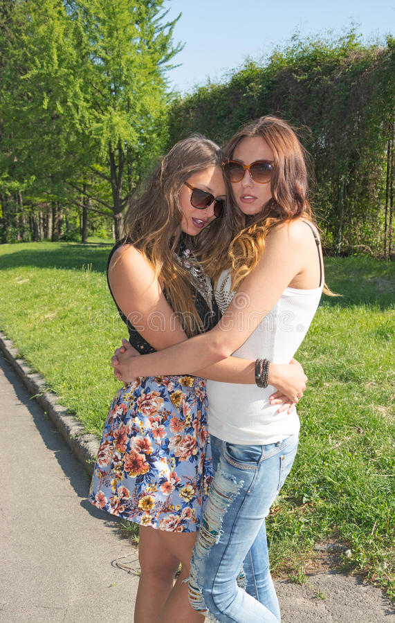两个美丽的女朋友放松公园 图库摄影