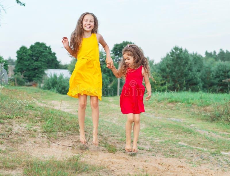 两个美丽的小女孩跳晴朗的夏日 机会 免版税库存图片