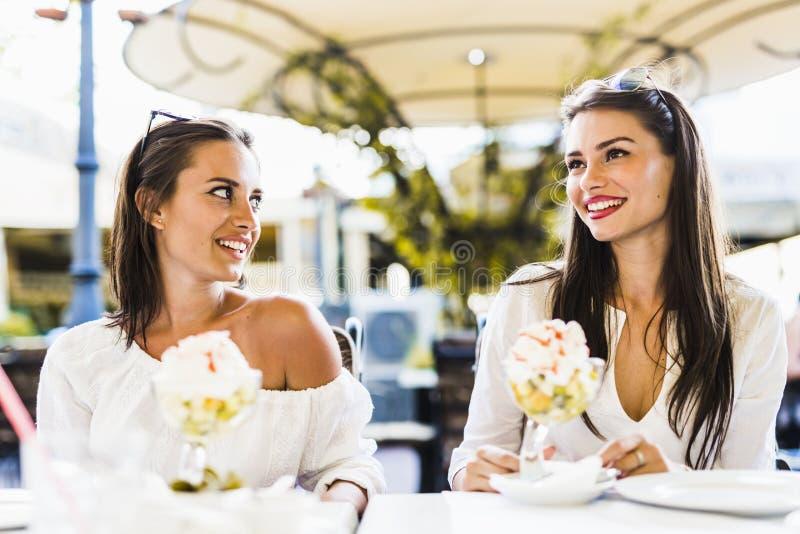 两个美丽的少妇微笑和饮用水果沙拉在a 图库摄影