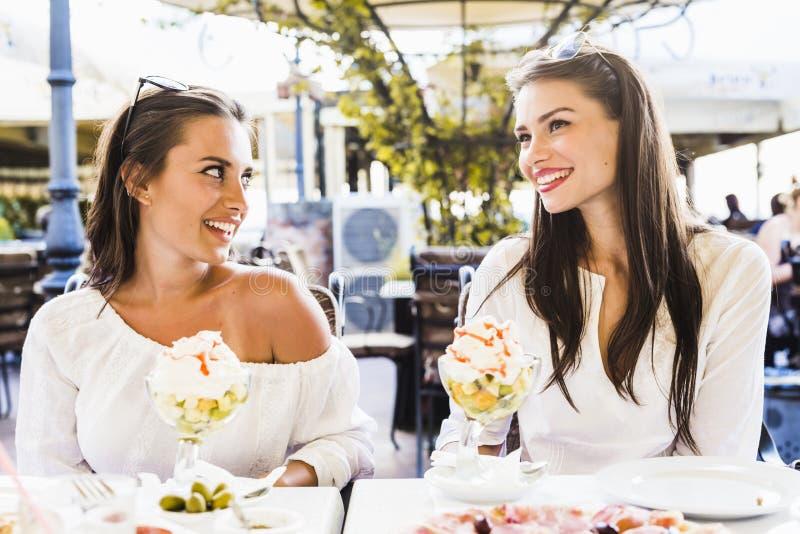 两个美丽的少妇微笑和饮用水果沙拉在a 库存照片