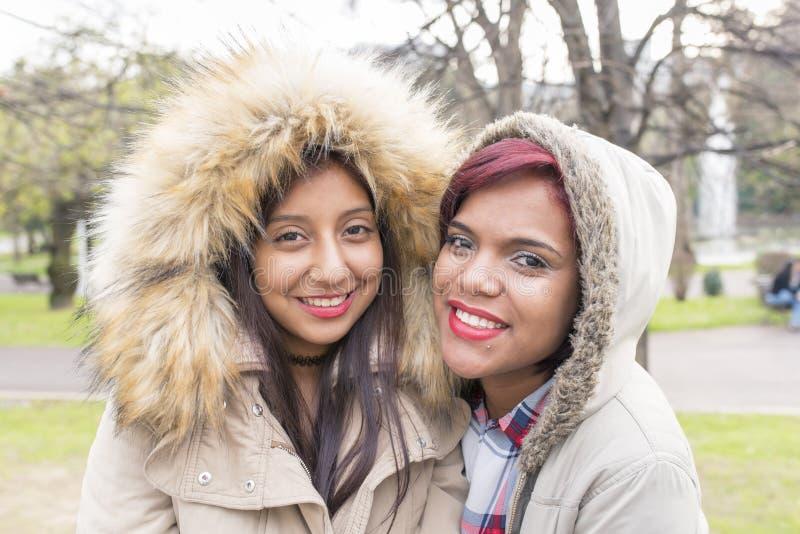 两个美丽的微笑的妇女朋友在公园 免版税库存照片