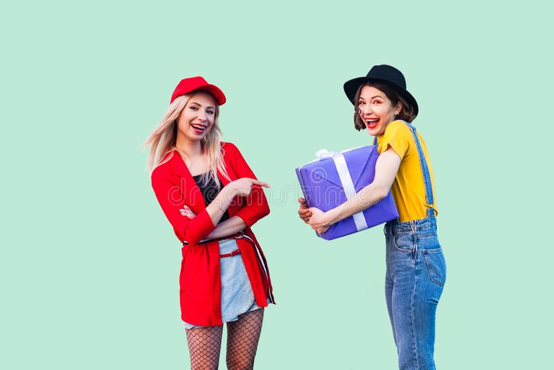 两个美丽的愉快的时兴的行家最好的朋友,拥抱大紫罗兰色箱子礼物和暴牙的微笑,金发碧眼的女人指向的愉快的女孩 免版税库存照片