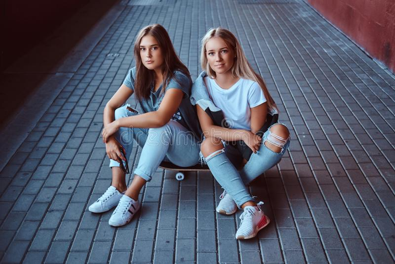 两个美丽的行家女孩坐滑板在边路在桥梁下 免版税库存图片