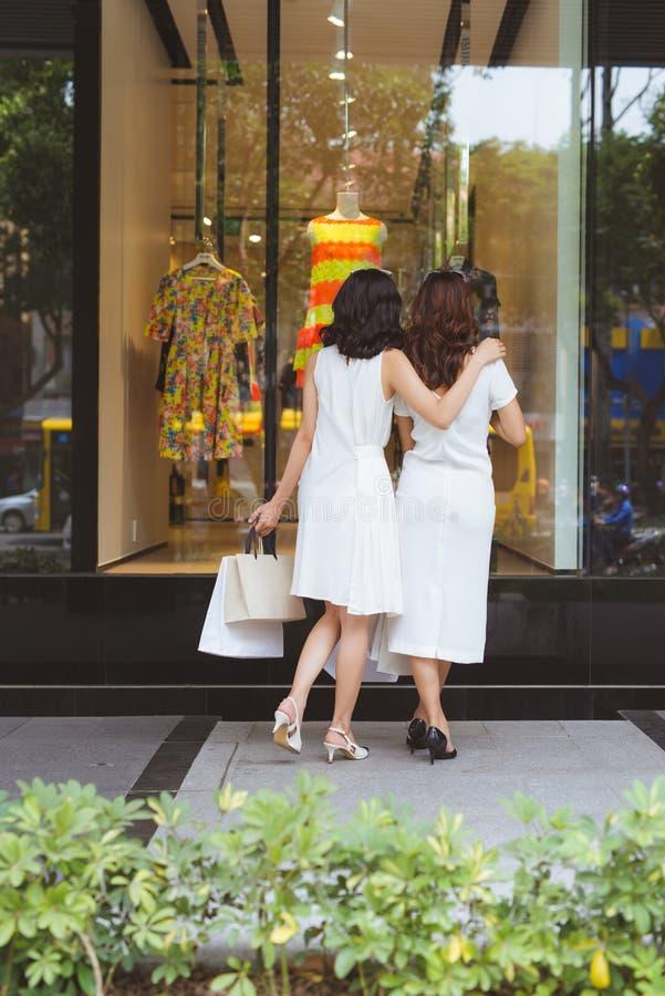 两个美好的女孩窗口购物在城市 免版税库存图片