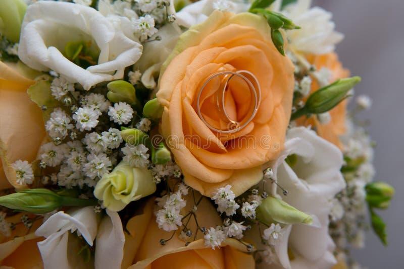 两个美好的婚戒在有花的一个茶碟说谎 库存图片