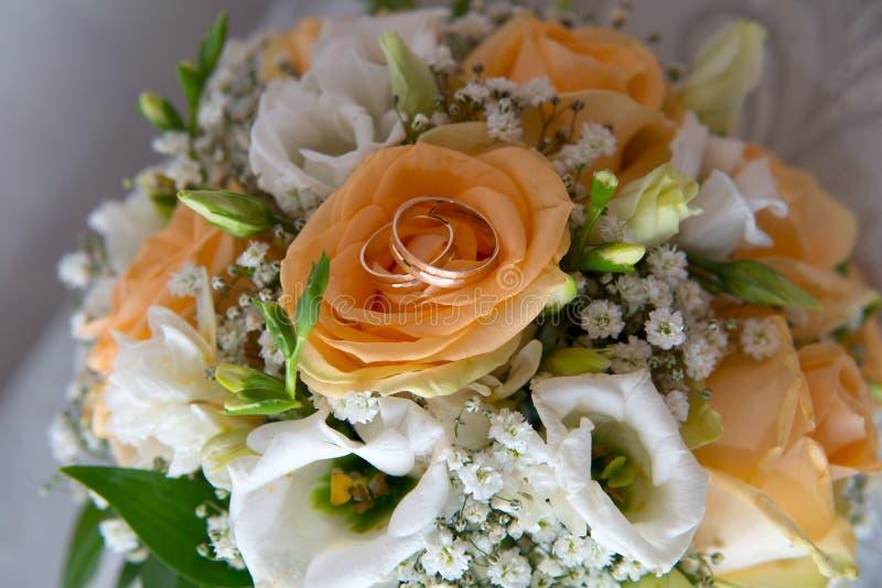 两个美好的金子婚戒在有花的一个茶碟说谎 库存照片
