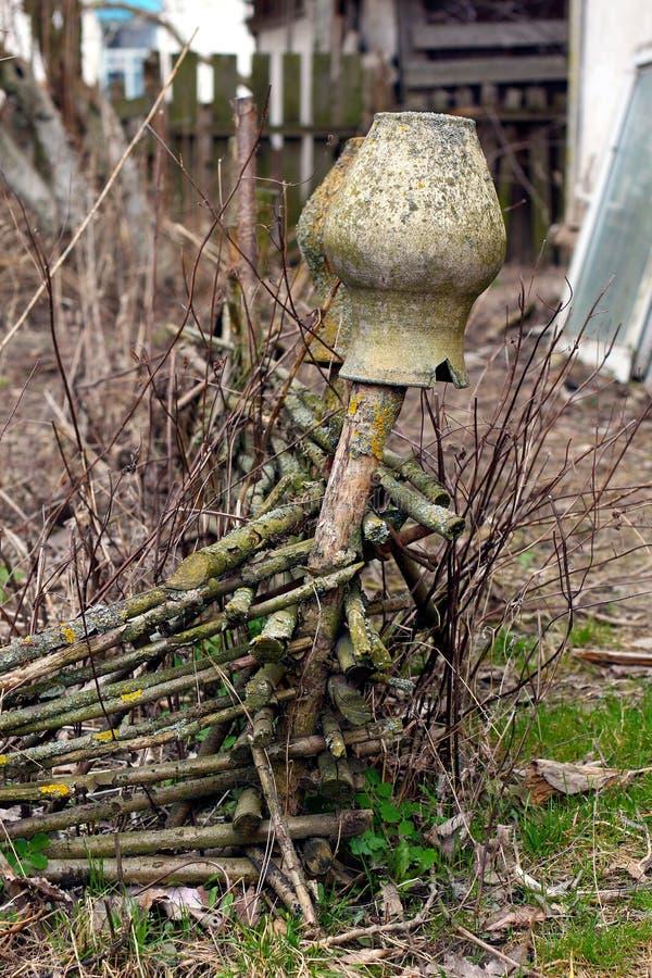 两个老黏土水罐在柳条篱芭垂悬 免版税库存照片