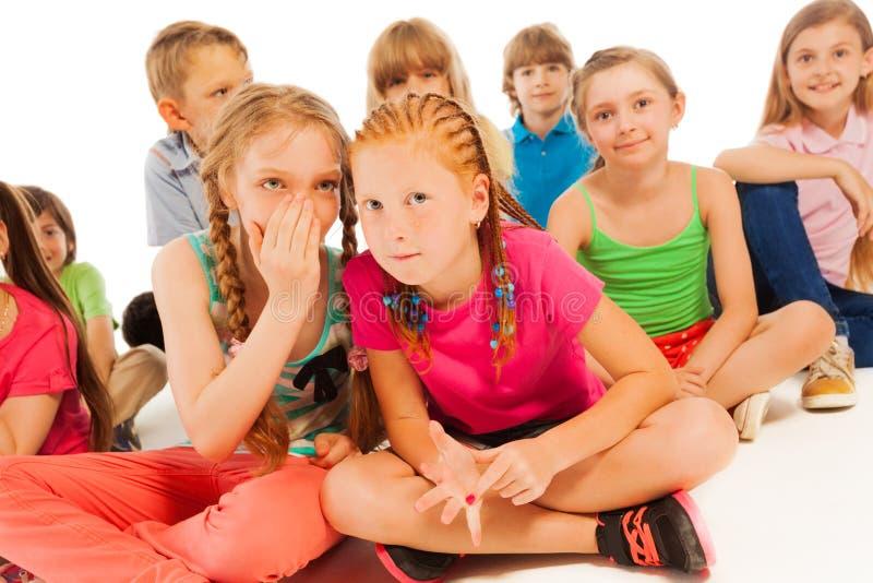 两个耳语的女孩坐在其他朋友中 库存图片