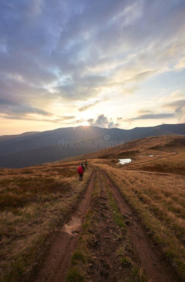 两个背包徒步旅行者在山的足迹跌倒 免版税库存照片