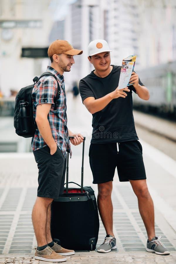两个背包徒步旅行者看一张地图火车站 汽车城市概念都伯林映射小的旅行 免版税库存图片